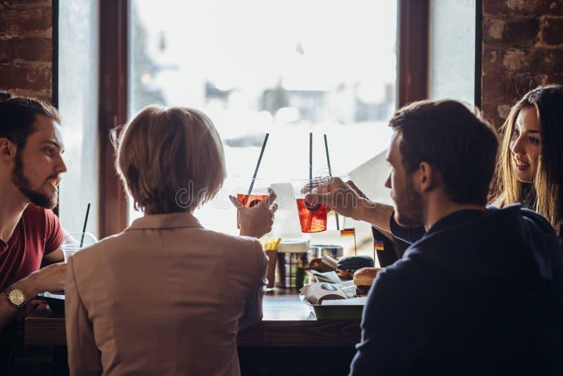 Задний взгляд компании молодых счастливых людей говоря пока сидящ на кафе стоковая фотография
