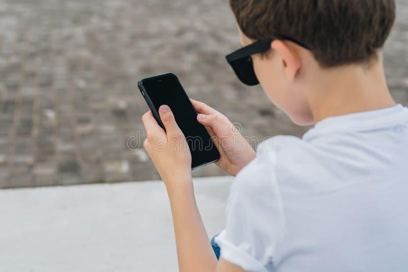 задний взгляд Конец-вверх smartphone в руках мальчика Подросток сидит внешнее, использует устройство, интернет просматривать, про стоковые фото