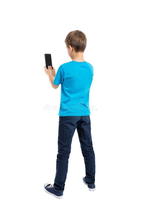 Задний взгляд мальчика в футболке и джинсах говоря на мобильном телефоне стоковое фото rf