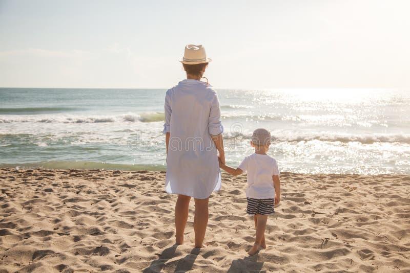Задний взгляд матери и сына на пляже на солнечном дне пристаньте детенышей к берегу тропической каникулы песка семьи 4 белых стоковая фотография