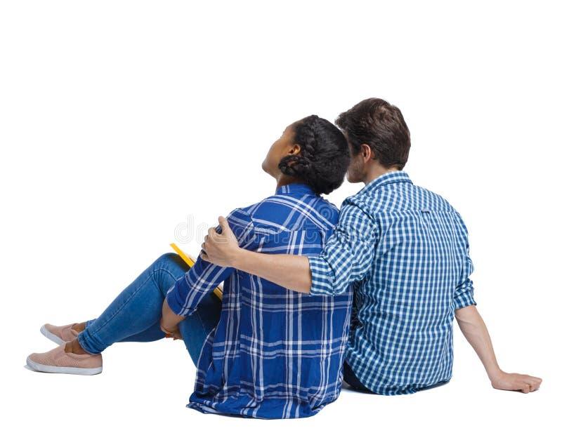 Задний взгляд многонациональной молодой пары сидя на том основании и обнимая стоковые изображения
