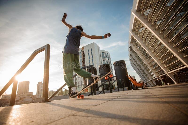Задний взгляд молодого активного человека скача на скейтборд против стоковое изображение