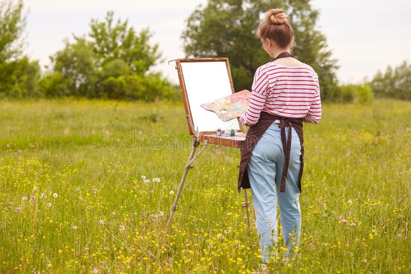 Задний взгляд молодого тонкого изображения чертежа художника женщины на холсте в природе, девушке с щеткой в руке и палитре красо стоковая фотография