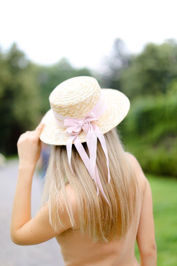 Задний взгляд молодой белокурой девушки в прозодеждах и шляпе пигмента стоковые изображения