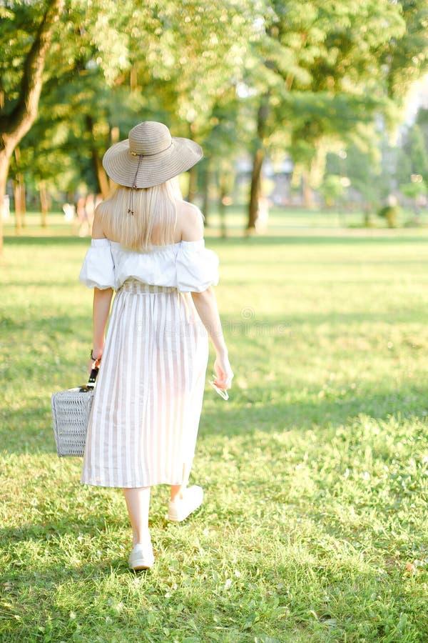 Задний взгляд молодой женщины в шляпе идя в парк и держа сумку стоковое изображение rf