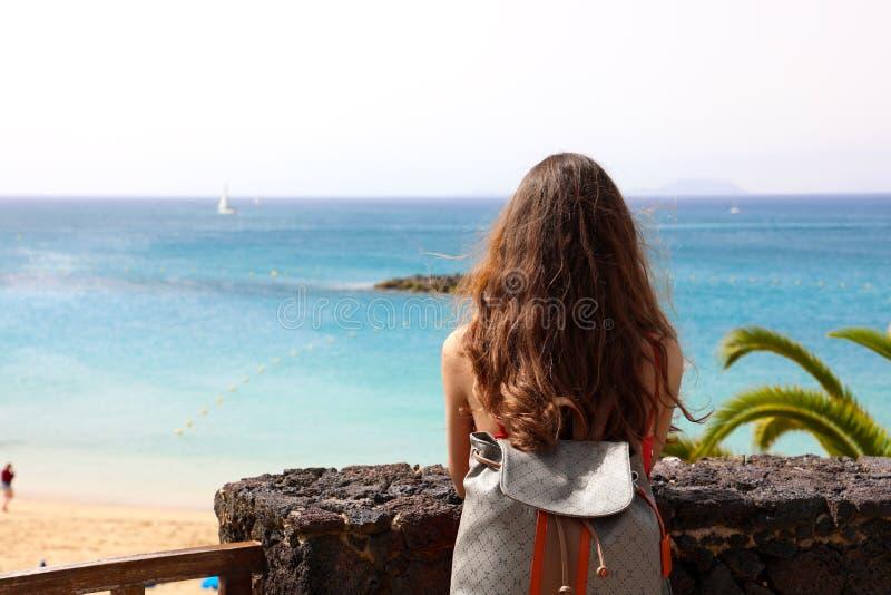 Задний взгляд молодой женщины при рюкзак смотря к пляжу рая, Лансароте, Канарским островам стоковое изображение