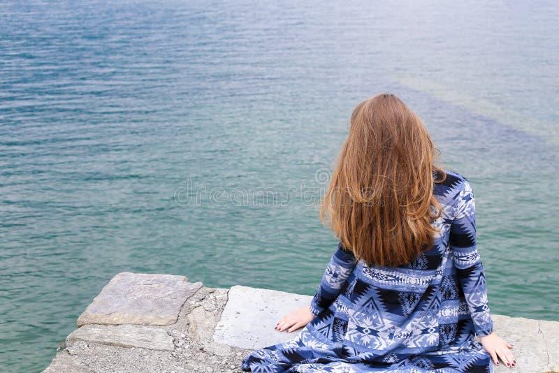 Задний взгляд молодой женщины сидя около озера Como, воды в предпосылке стоковое изображение rf