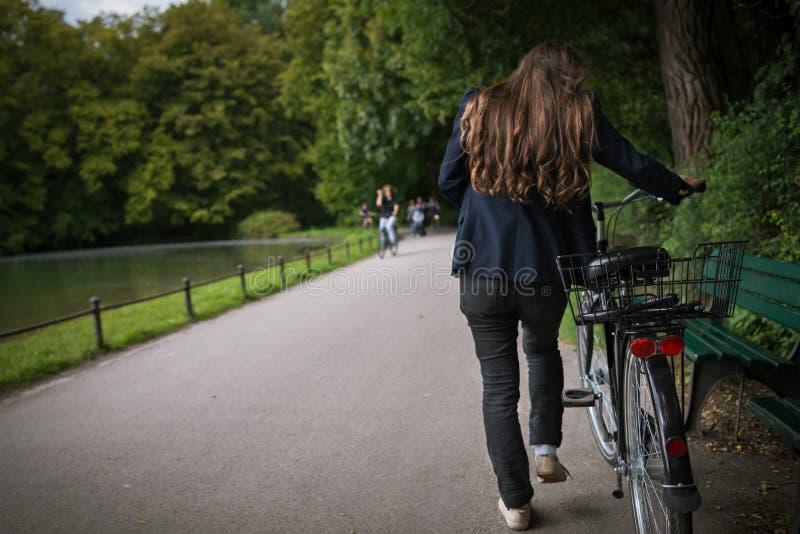 Задний взгляд молодой женщины с велосипедом в парке на предпосылке деревьев стоковые фотографии rf