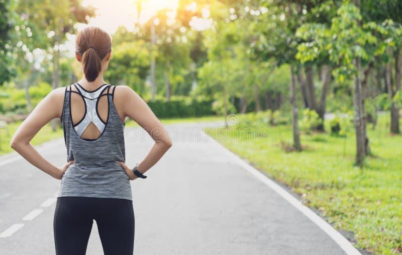 Задний взгляд молодой женщины фитнеса бежать на дороге в утре, молодом бегуне спортсменки фитнеса бежать на тропическом tra парка стоковые фотографии rf