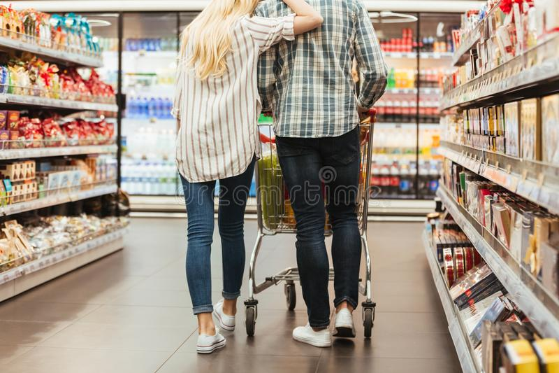 Задний взгляд молодой пары идя с вагонеткой стоковые изображения rf