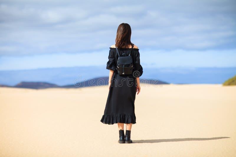 Задний взгляд молодой сиротливой женщины в длинном черном платье в пустыне дальше стоковые изображения