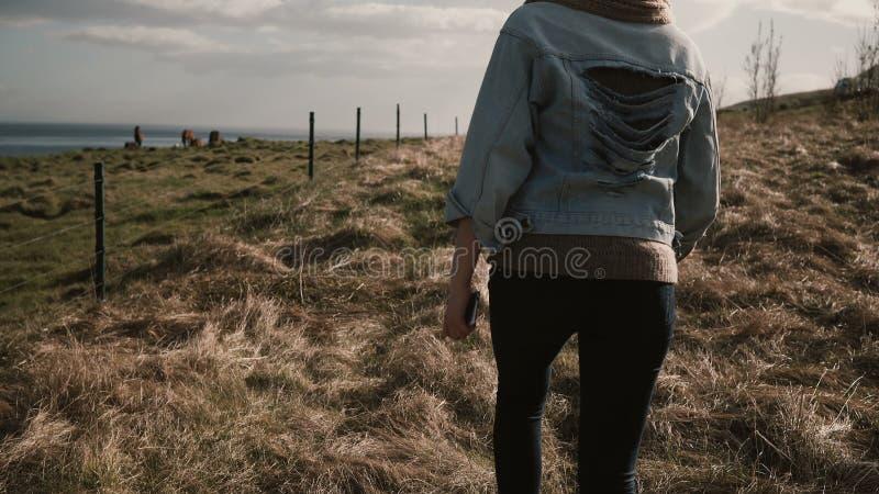 Задний взгляд молодой стильной женщины идя на природу, вне города через поле около лошадей обрабатывает землю стоковые фотографии rf