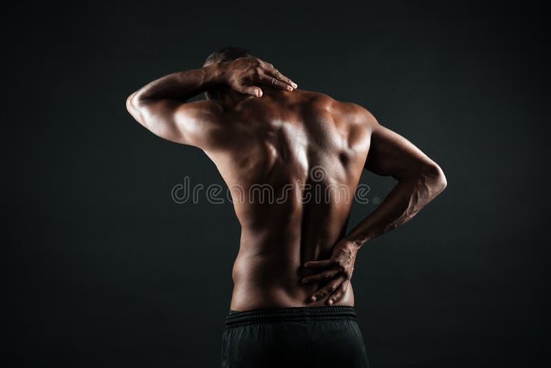 Задний взгляд молодых африканских спорт укомплектовывает личным составом боль чувства в его назад стоковое изображение