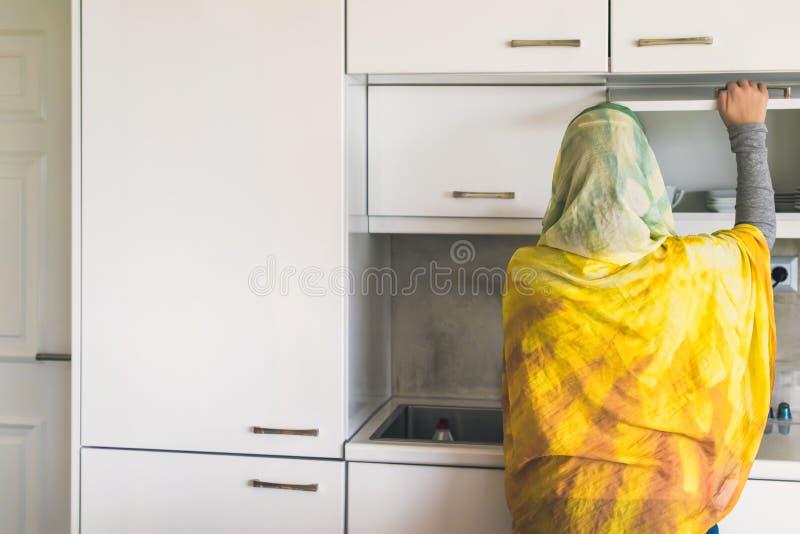 Задний взгляд на мусульманской женщине в шарфе раскрывает дверь шкафа whte с чашками и плитами стоковое фото rf