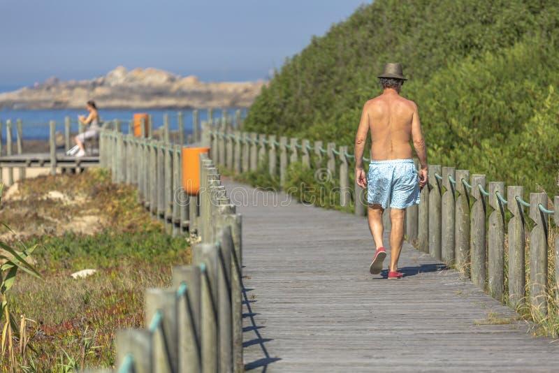 10 04 2018: Задний взгляд на человеке, идя на путь eco пешеходный, около моря, Португалия стоковое изображение
