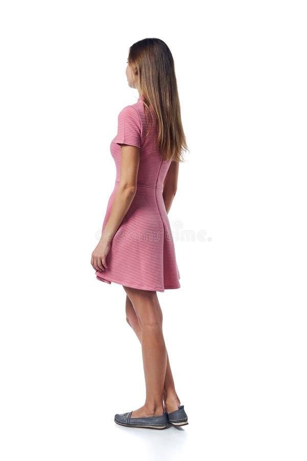Задний взгляд полнометражный молодой женщины в розовом платье стоя случайно стоковая фотография