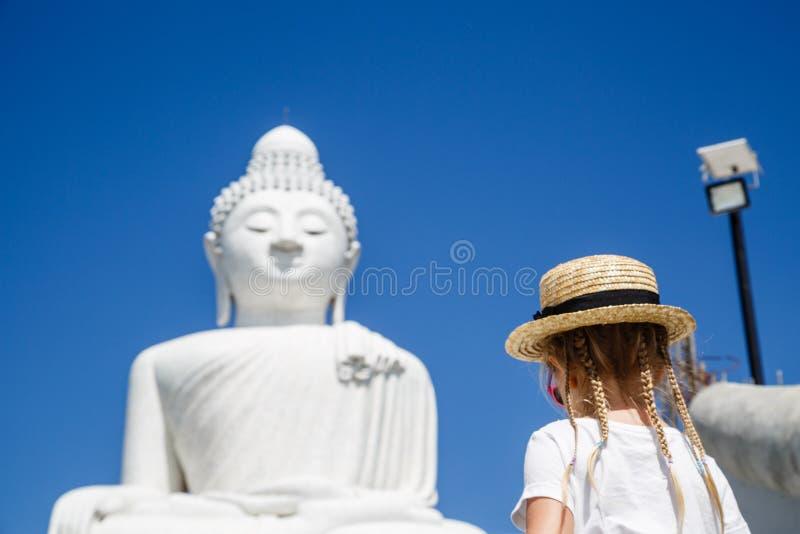Задний взгляд положения маленькой девочки около большой статуи Будды в Пхукете, Таиланде Концепция туризма в Азии и известное стоковые фото
