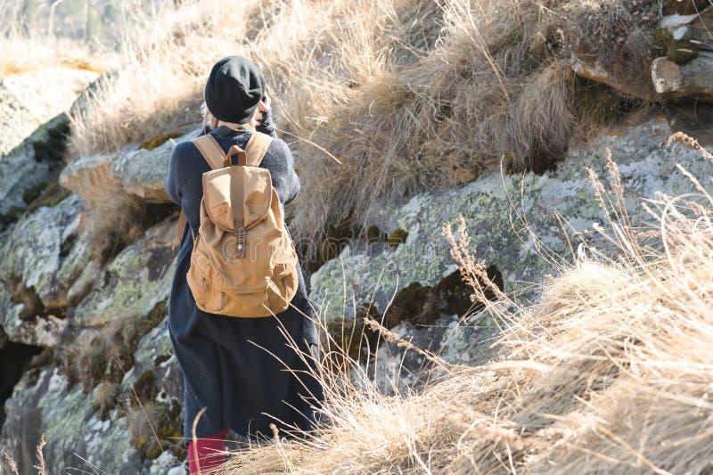 Задний взгляд привлекательного женского туриста, стоя в шляпе с рюкзаком на ее плечах наслаждаясь солнечным после полудня стоковые фотографии rf