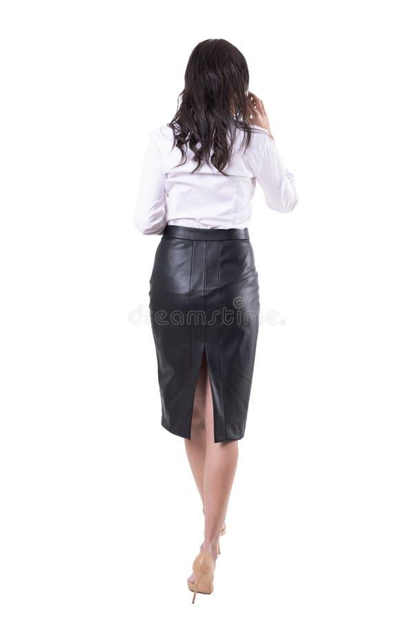 Задний взгляд привлекательной бизнес-леди говоря по телефону идя в спешку или спешность стоковые фото