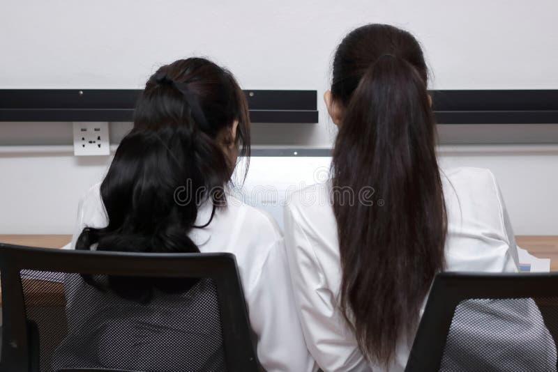 Задний взгляд привлекательной молодой азиатской коммерсантки 2 используя компьтер-книжку совместно в современном офисе Концепция  стоковые фотографии rf