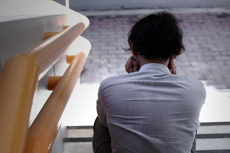Задний взгляд разочарованного усиленного молодого азиатского чувства бизнесмена попробованного или вымотанного на лестницу офиса стоковое фото
