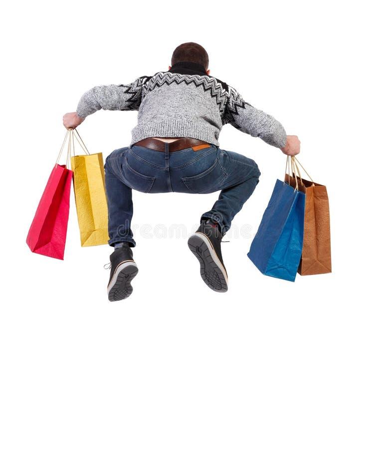 Задний взгляд скача человека в свитере с хозяйственными сумками которые бега стоковые фотографии rf
