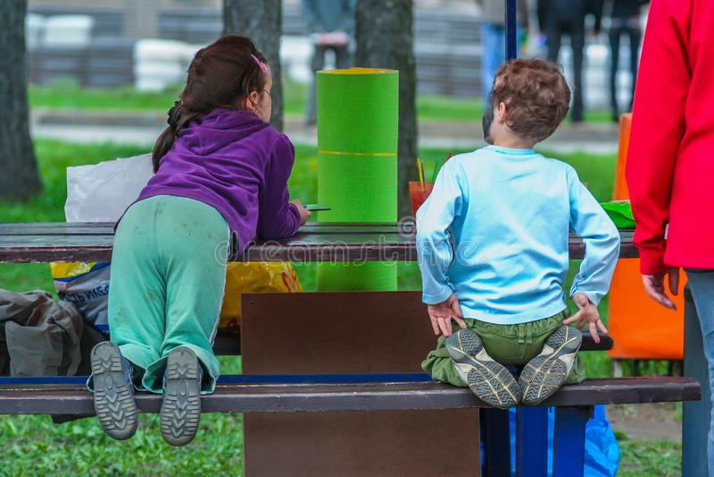 Задний взгляд со стороны мальчика и девушки сидя на стенде таблицей стоковое изображение