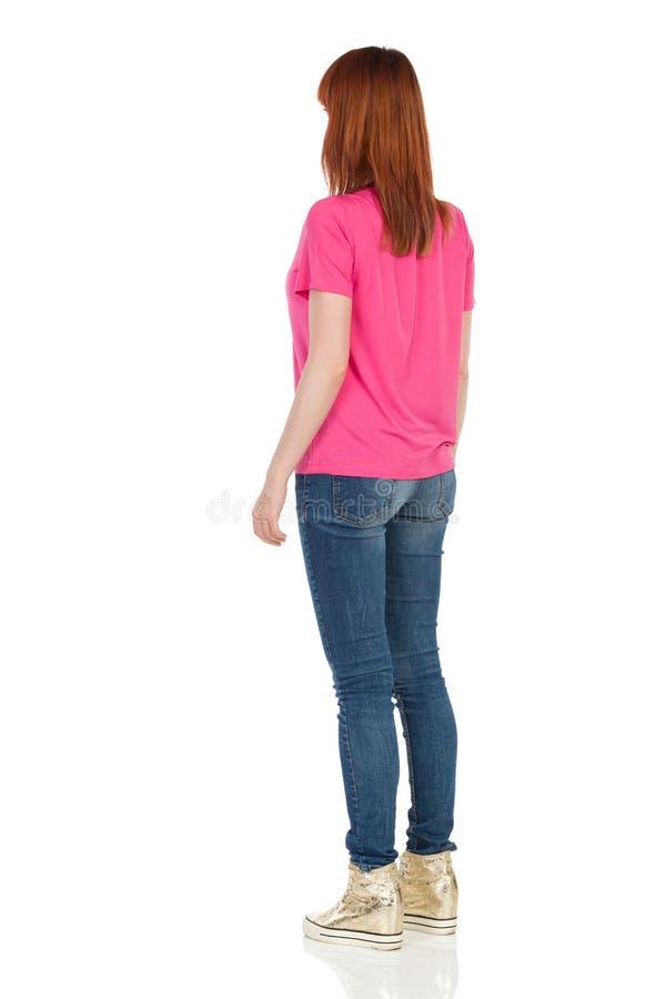 Задний взгляд со стороны молодой стоящей женщины в розовой рубашке стоковые изображения
