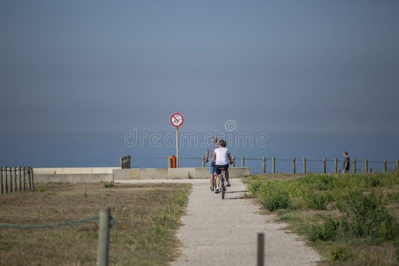 Задний взгляд средн-достигших возраста пар, задействуя на пути пешехода/велосипеда eco, около моря стоковые изображения rf