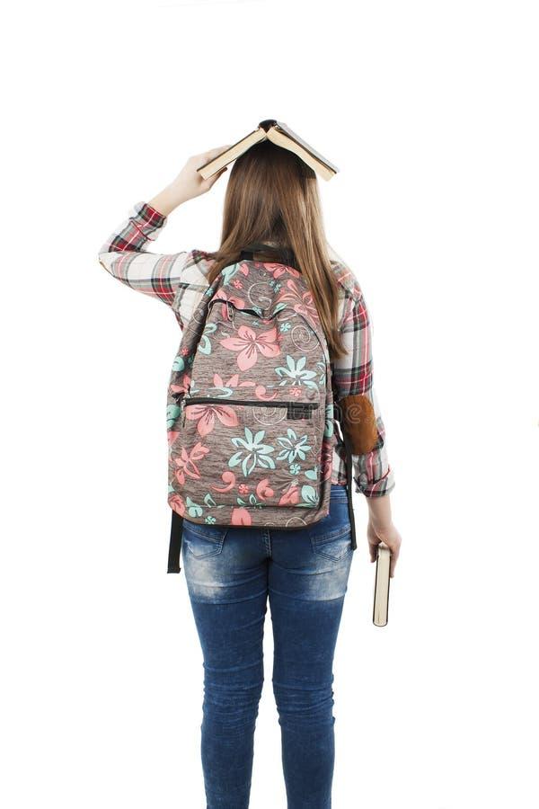 Задний взгляд студентки, держа книгу на голове стоковая фотография