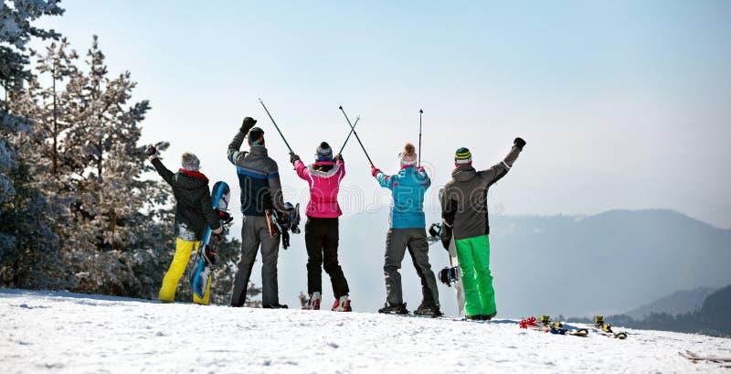Задний взгляд счастливой катаясь на лыжах группы на верхней части горы стоковая фотография