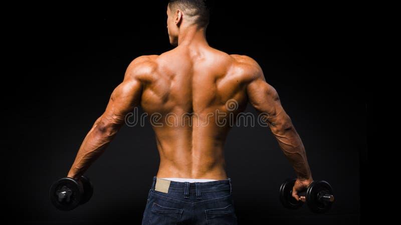 Задний взгляд тренировки портрета молодого человека без рубашки с гантелью против черной предпосылки стоковые фото