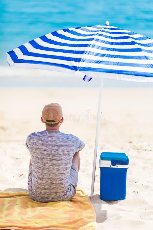 Задний взгляд туристского усаживания на пляже под зонтиком около охладителя с холодными напитками Фотография каникул релаксации п стоковые изображения rf