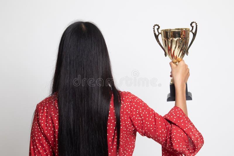 Задний взгляд успешной молодой азиатской женщины держа трофей стоковое изображение