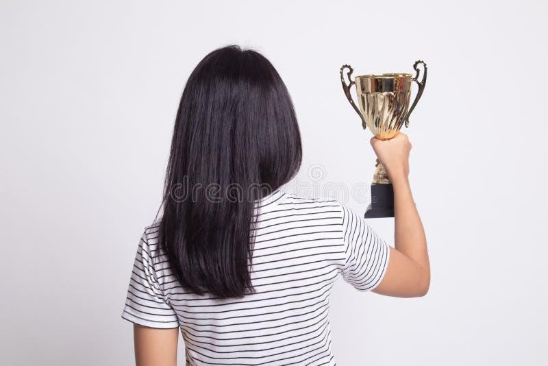 Задний взгляд успешной молодой азиатской женщины держа трофей стоковые фотографии rf