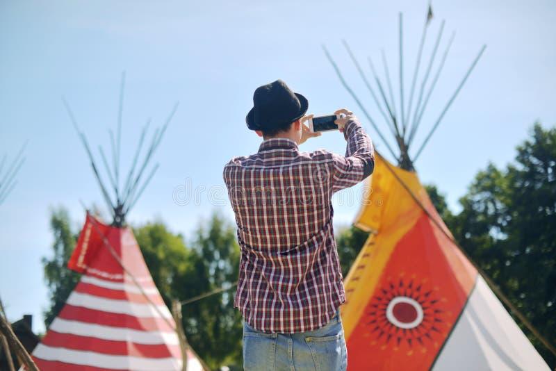 Задний взгляд фото молодого человека туристского принимая дома teepee/типи родного индийского с smartphone Принимать фото живой п стоковая фотография rf