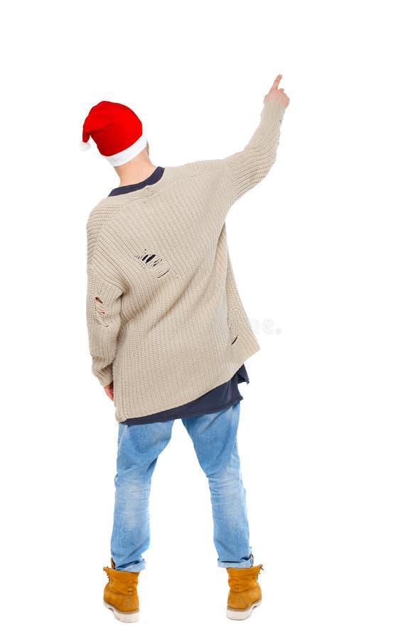 Задний взгляд человека в шляпе Санта Клауса указывая вверх стоковая фотография rf