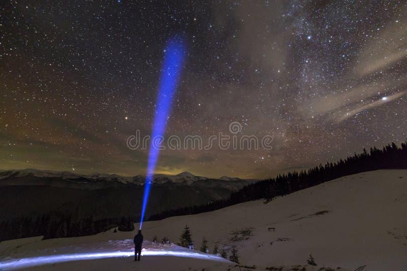Задний взгляд человека с главным положением электрофонаря на снежной долине под небом красивой темно-синей зимы звездным, ярким г стоковое изображение