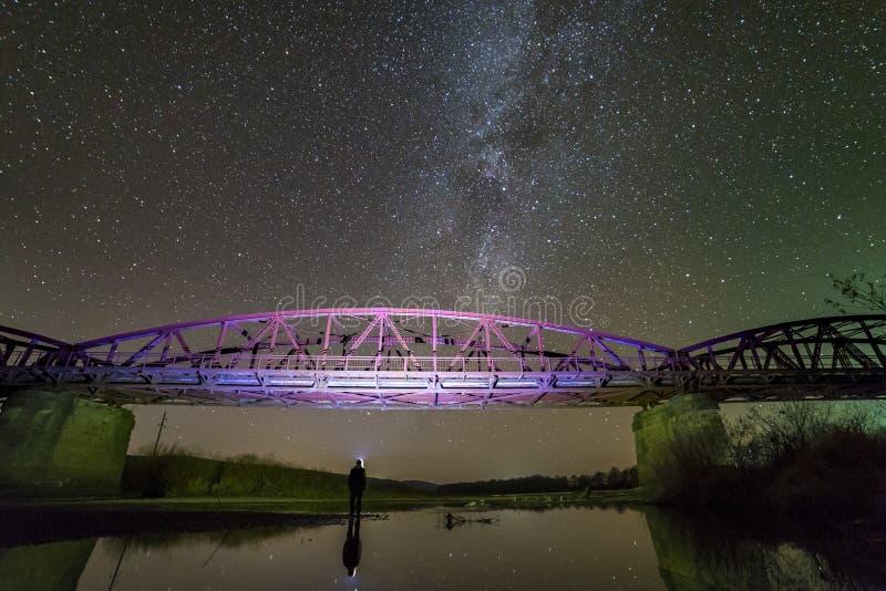 Задний взгляд человека с положением электрофонаря на речном береге под загоренным мостом металла под темным звездным небом отраже стоковые изображения