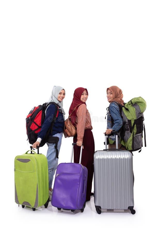 Задний взгляд, чемодан удерживания положения женщины 3 hijab и сумка нося стоковое фото rf