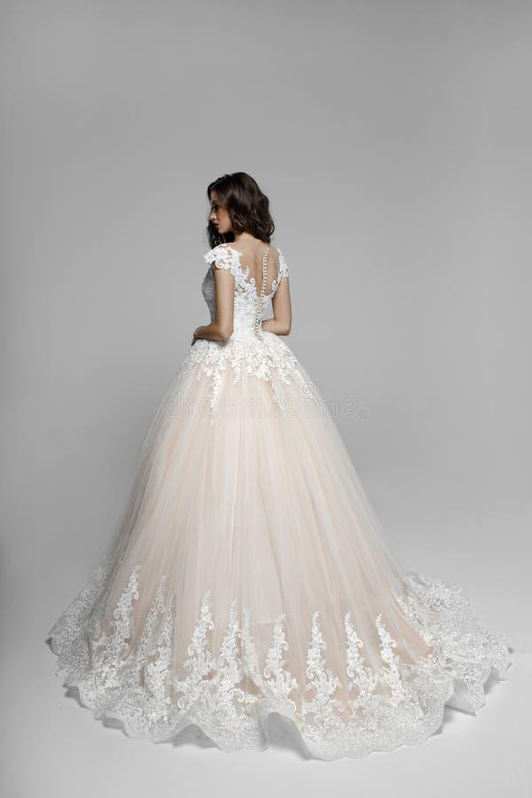 Задний взгляд элегантно молодой женщины в красивом wendding платье, изолированный на белой предпосылке стоковые изображения rf