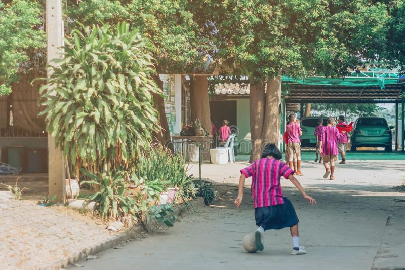 Задний взгляд юбки носки студента девушки, который нужно напрактиковать сыграть футбол самостоятельно на улице стоковое изображение rf
