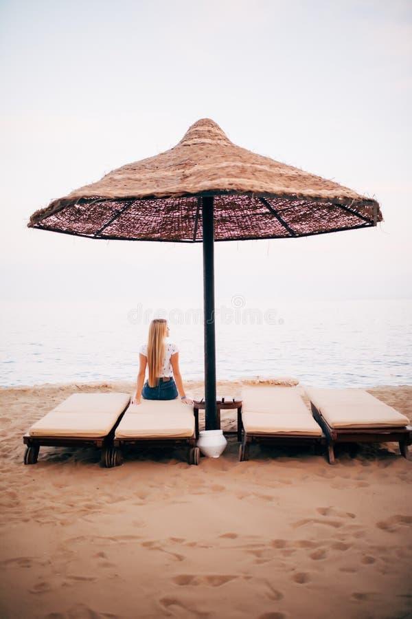 Задний взгляд Deckchairs, Loungers Солнця под зонтиком на пляже песка Женщина ослабляя на креслах для отдыха под шатром морским п стоковые фото