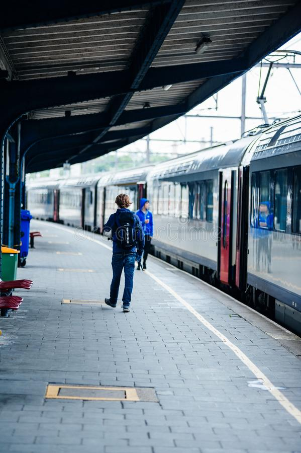 Задний вид молодого мужчины на железнодорожной платформе стоковые изображения