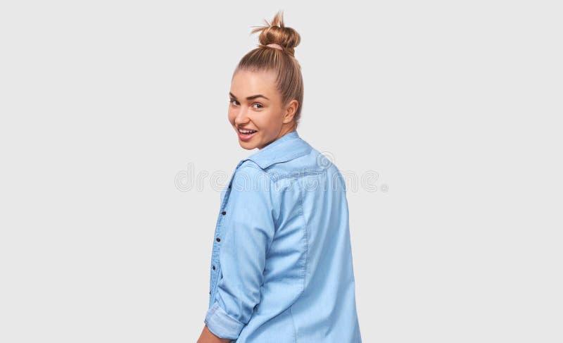 Задний вид на красивую молодую женщину, широко и положительно улыбающуюся в синей случайной рубашке и глядя на камеру, изолирован стоковое изображение rf