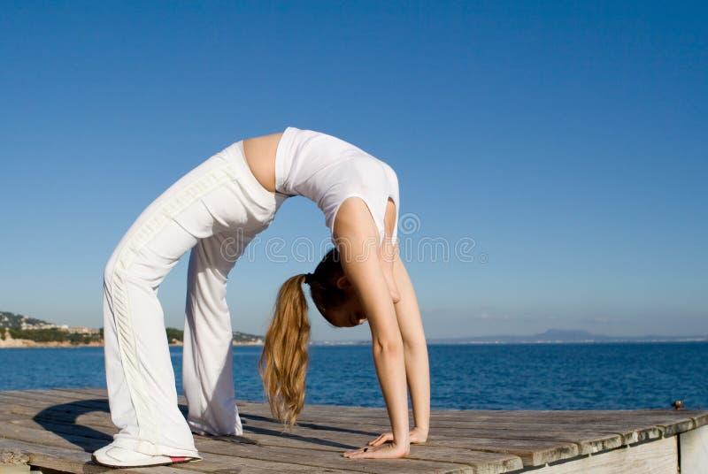 задний загиб делая подходящую здоровую женщину стоковое фото rf