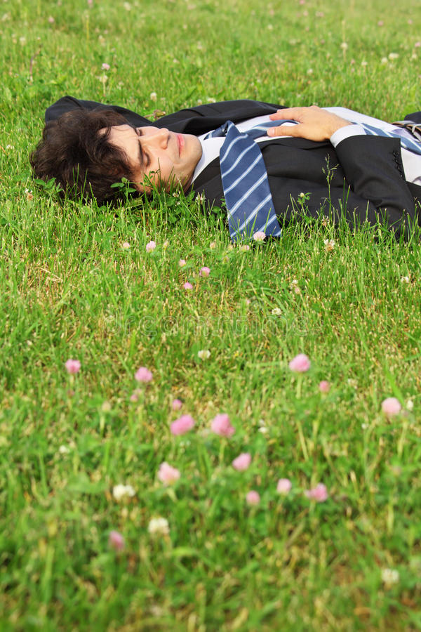 задний закрынный бизнесмен eyes лож травы стоковое изображение