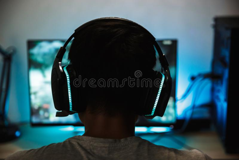 Задний крупный план взгляда молодого мальчика gamer играя видеоигры онлайн стоковая фотография rf