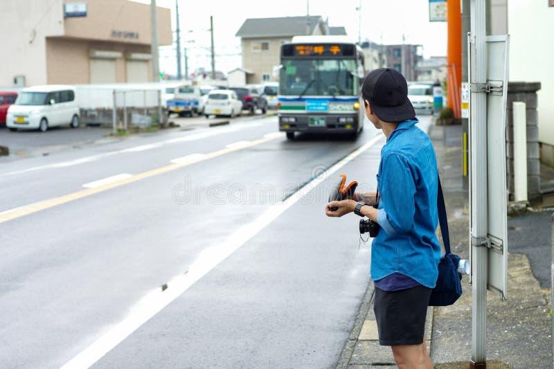 Задний портрет автобуса неопознанного мужского туриста ждать приходя стоковые изображения rf