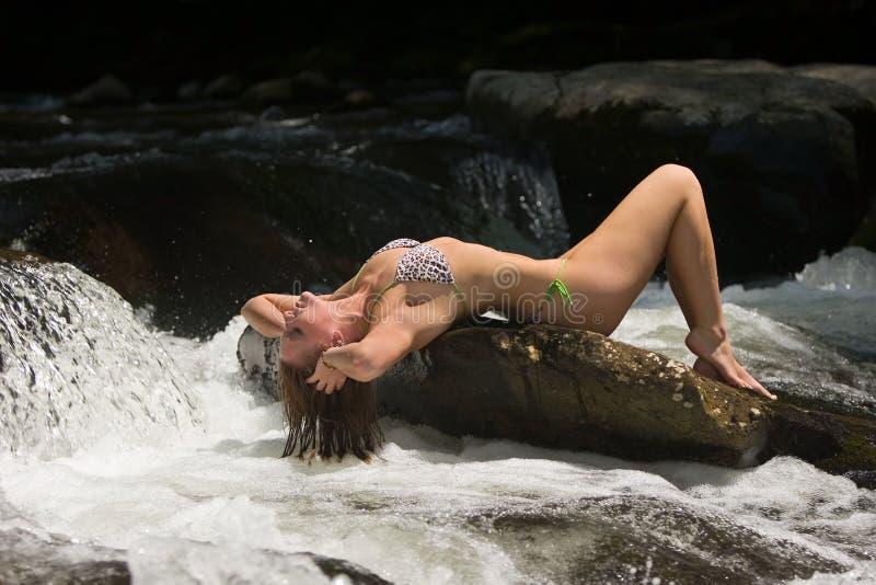 задняя девушка бикини ее whitewater наклоненное утесом стоковое фото rf